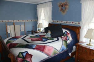 The Country Room with the light blue wallpaper and a homemade quilt on the bed.