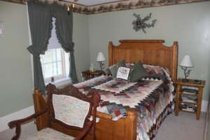The woods room with lite green walls and a homemake quilt on the bed.