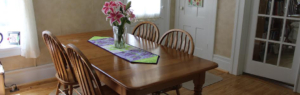 A photo of the dining room table with a vase with flowers in it.